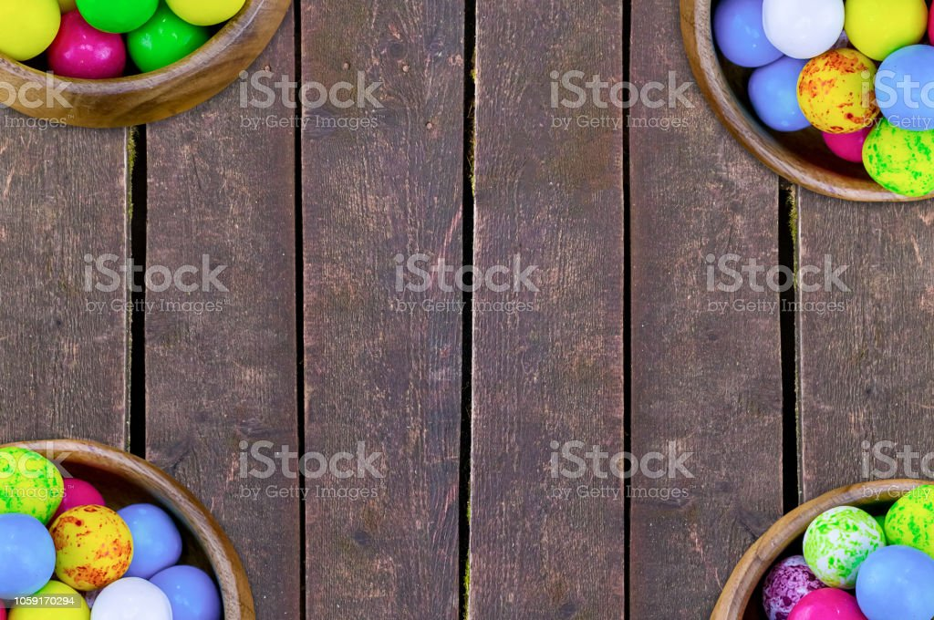 set four bowls of colorful bright round sweet candies yellow blue blue white on a vertical board background stock photo