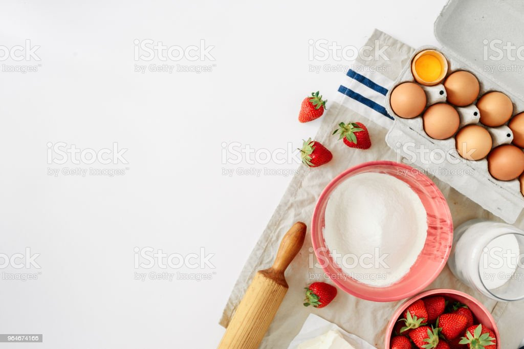 Set ingredients for cooking strawberry pie or cake on white background with border. Flat lay, top view. Eggs, flour, milk, sugar, strawberry, top view. Bakery background. Recipe for strawberry pie. Rustic style royalty-free stock photo