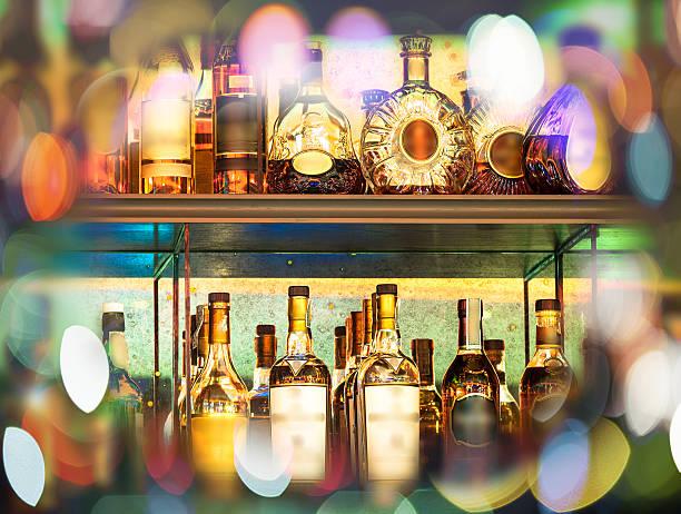 ensemble de bouteilles d'alcool sur le mur avec bokeh - spiritueux photos et images de collection