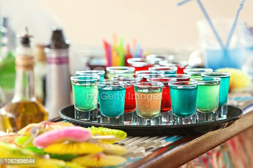 Colorful cold cocktails shots on the tray. Variation of hard alcoholic alcoholic drink in different colors. Day party.