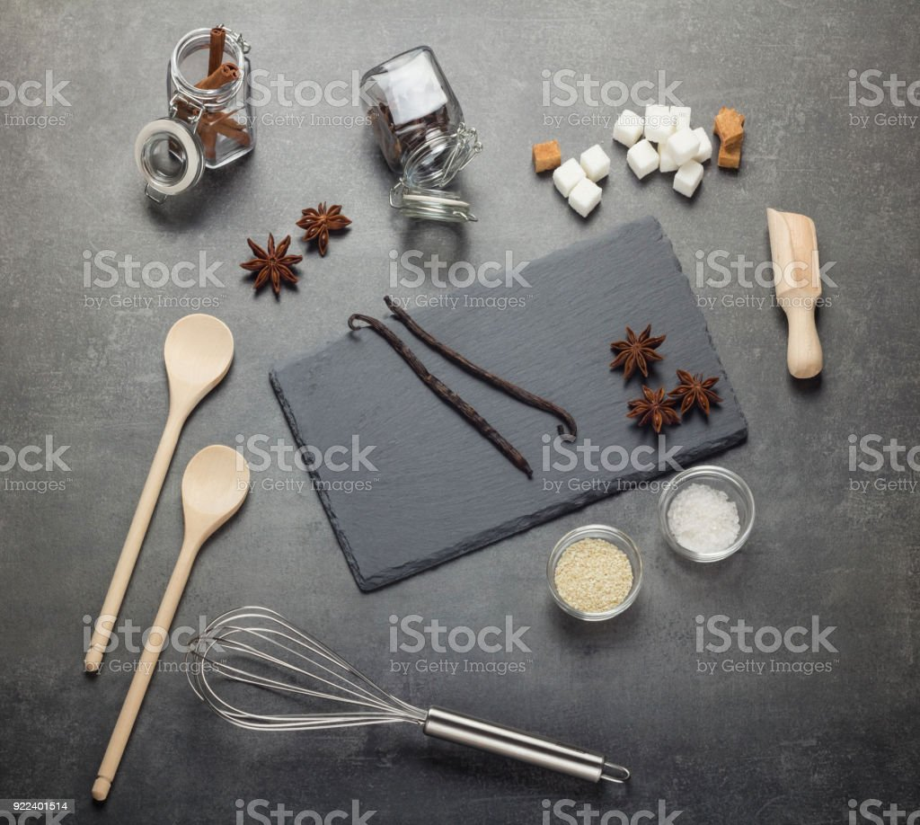 Set of aromatic spices, sesame seeds, salt, sugar and kitchenware, on gray stock photo