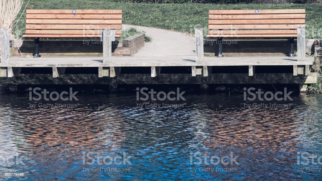 A set of benches overlooking a beautiful lake - Royalty-free Bench Stock Photo