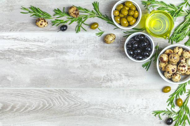 set von schwarze und grüne oliven, eier wachtel auf platten, olivenöl und rosmarin - wachtelei stock-fotos und bilder