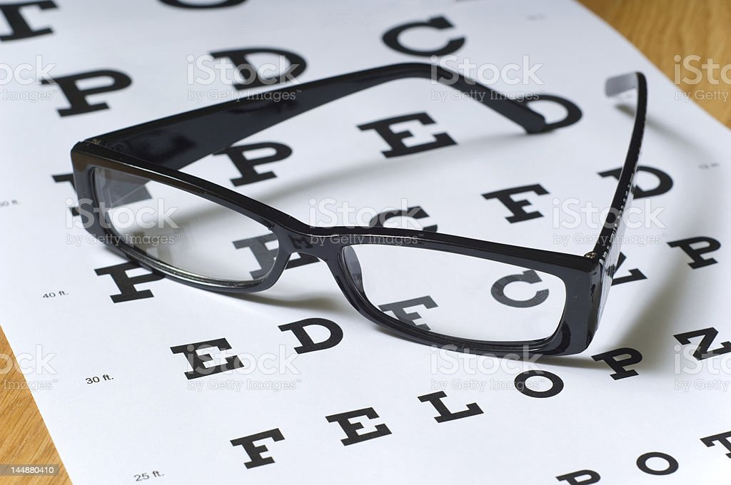 Set of black eyeglasses sitting on exam board stock photo