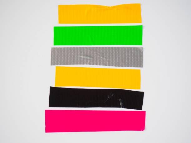 satz von schwarz grau gelb grün rosa klebrigen bändern auf weißem hintergrund. zerrissene horizontale und verschiedene größe klebeband, klebestücke. - aufkleber stock-fotos und bilder