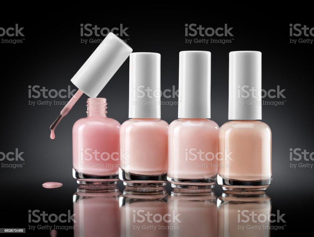 Set of bottles pearl colors nail polish on dark background Set of bottles pearl colors nail polish on dark background. Close up. Beauty concept Advertisement Stock Photo