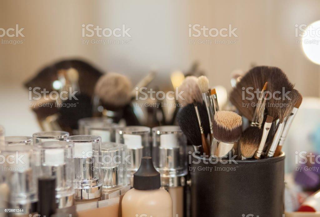 Set de pinceles para maquillaje y tono de la Fundación para la persona que está sobre la mesa delante de un espejo - foto de stock