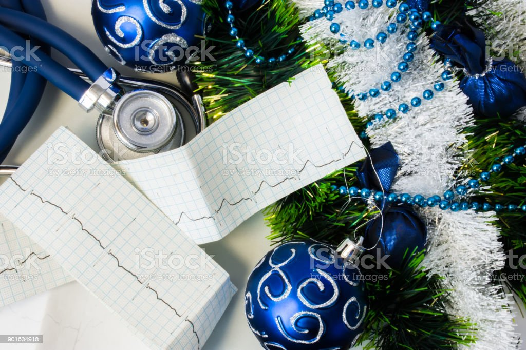 Set of cardiac diagnostic instruments with  Christmas or New Year decorations. Stethoscope and pulse trace ECG tape lying near artificial snow with glitter, toys and blue balls on Christmas tree stock photo