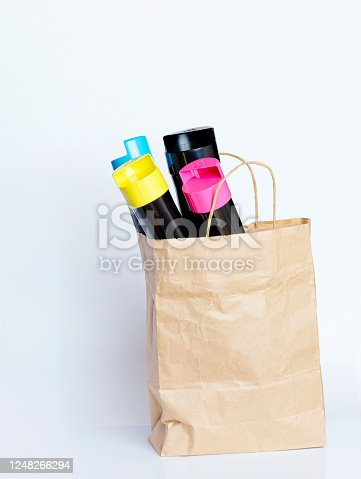 istock Set of cartridges for color laser printing in a paper bag on a gray background. 1248266294