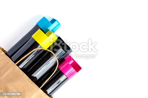 istock Set of cartridges for color laser printing lie on a table in a paper bag on a white background. 1248266296