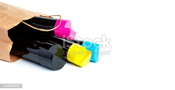 istock Set of cartridges for color laser printing lie on a table in a paper bag on a white background. 1248266301