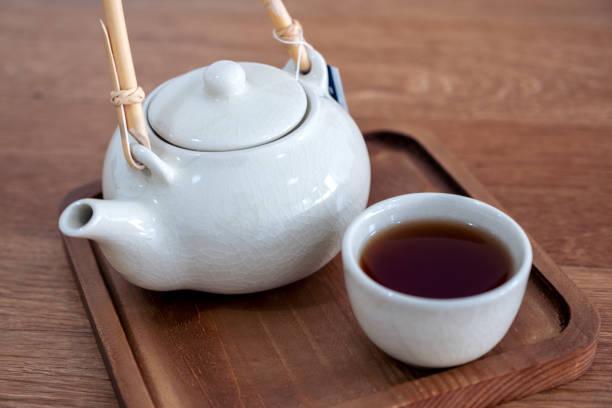 eine reihe von keramischen japanischen stil teekanne auf holz serviertablett - keramikteekannen stock-fotos und bilder