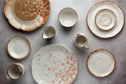 Set of ceramic round bowls and plates on vintage grey background