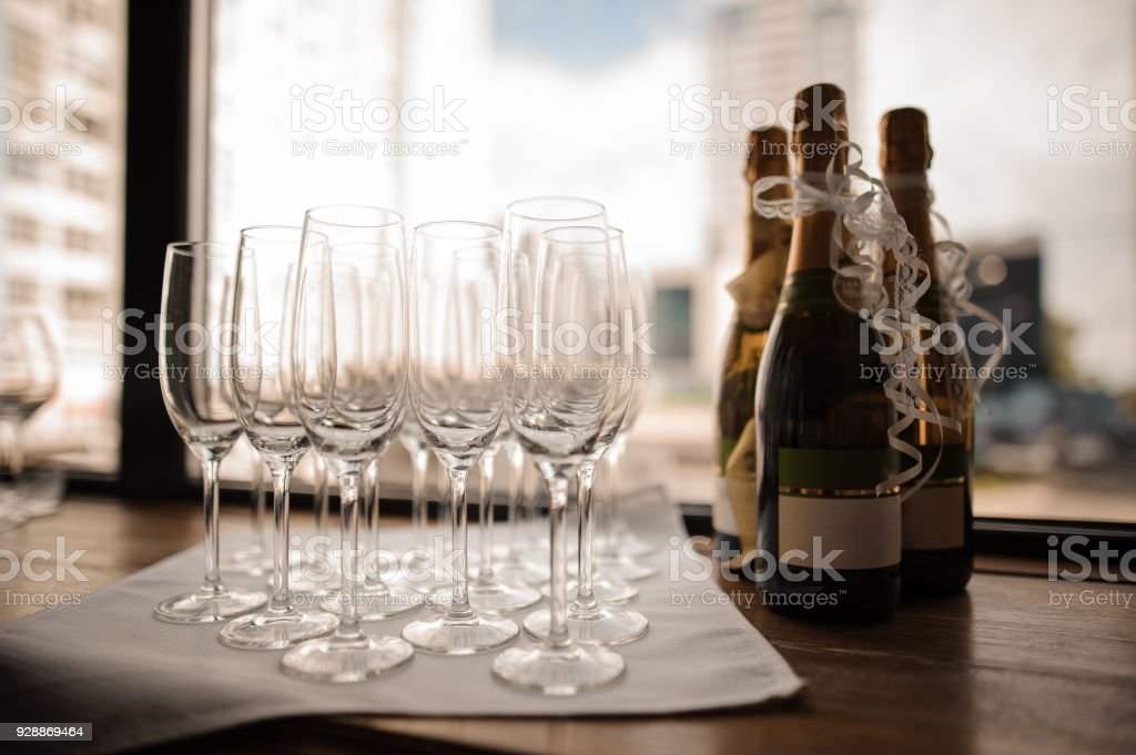 Set of champagne bottles and empty wine glasses on the serviette stock photo