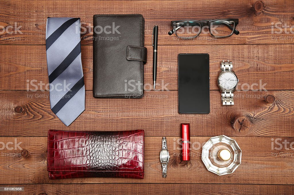 Set of classic man and woman accessories. Wallets, watches on wooden...