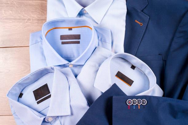 ensemble de vêtements classique mens - costume bleu, chemises, chaussures marron, ceinture et cravate sur fond en bois. - Photo