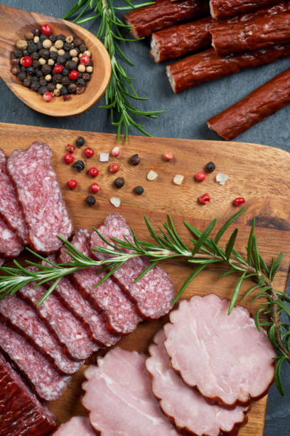Set of cold cuts on a wooden board. Mix of sausages stock photo