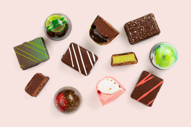 Set of coloful luxury handmade bonbons on pink background. Exclusive chocolate candies
