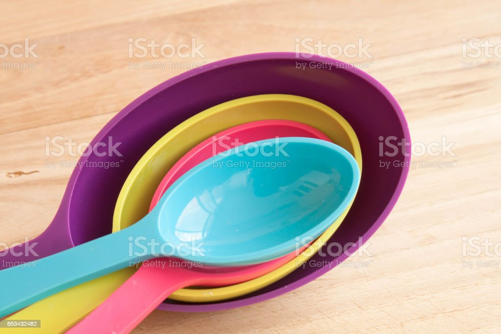 set of color measuring spoons in the cooking table stock photo