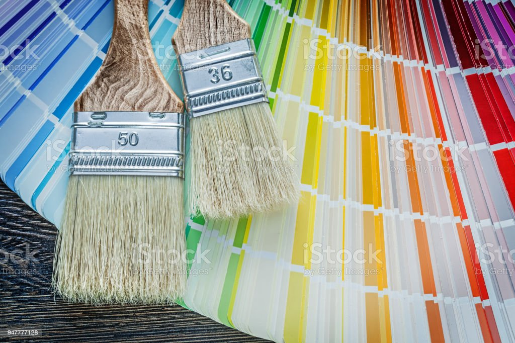Set of color sampler paintbrushes on wooden board stock photo