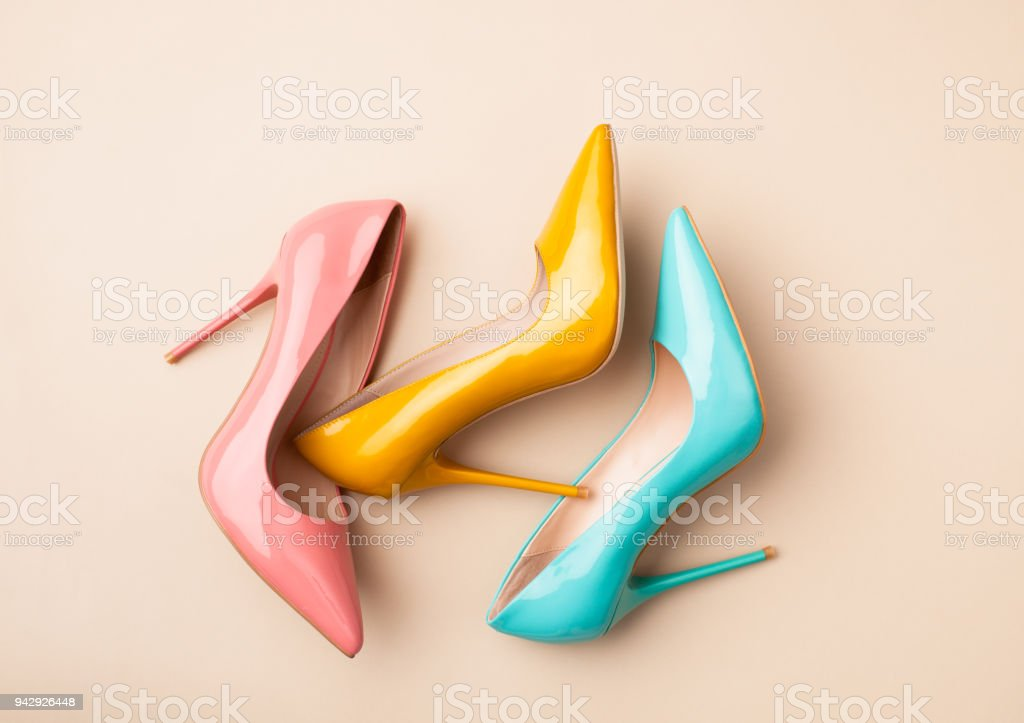 Set of colored women's shoes on beige background stock photo