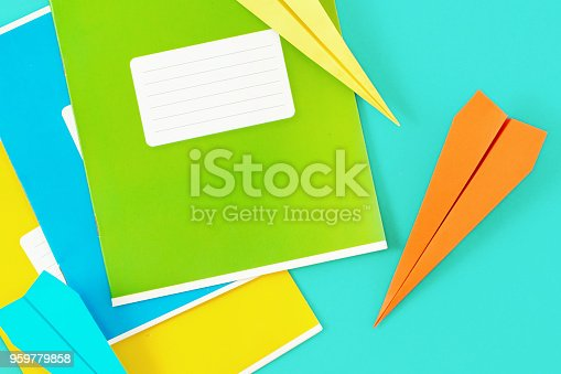 istock Set of colorful exercise books with paper airplane on blue background. Top view minimalist education background 959779858