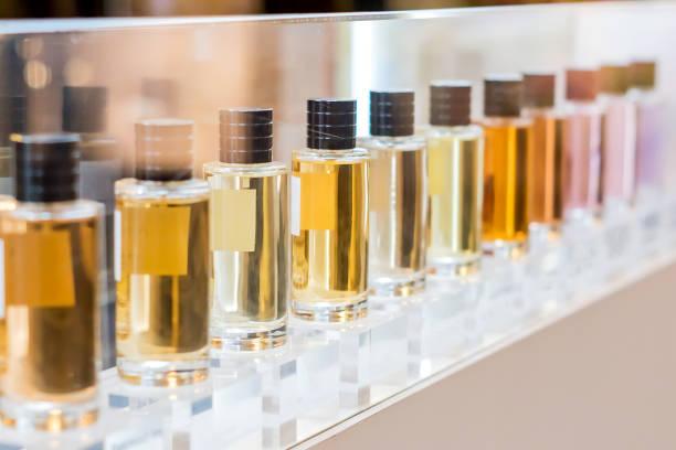 zestaw kolorowych butelek perfum w oknie sklepu - perfumowany zdjęcia i obrazy z banku zdjęć