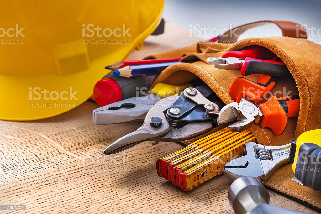 set of construction tools in toolbelt close up on wooden stock photo