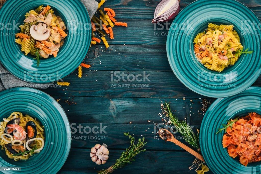 Um conjunto de pastas cozidas em placas. Sobre um fundo de madeira. Cozinha italiana. Vista superior. Copie o espaço. - Foto de stock de Almoço royalty-free