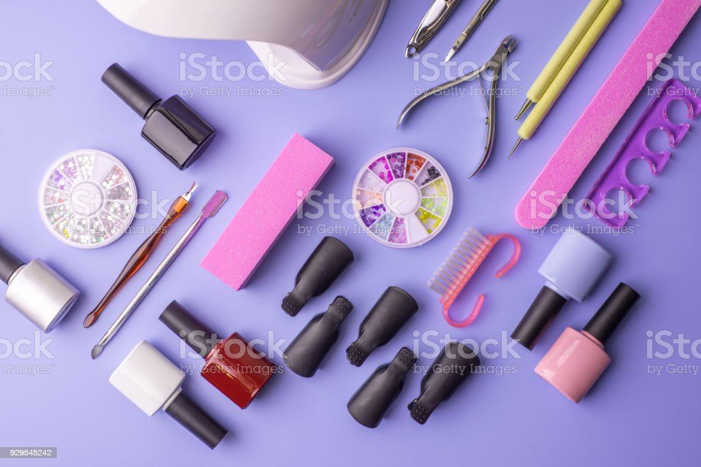Set of cosmetic tools for manicure and pedicure on a purple background. Gel polishes, nail files and clippers, top view stock photo