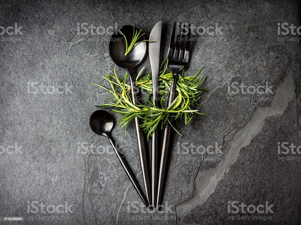 Set of cutlery and rosemary on black stone slate background. stock photo