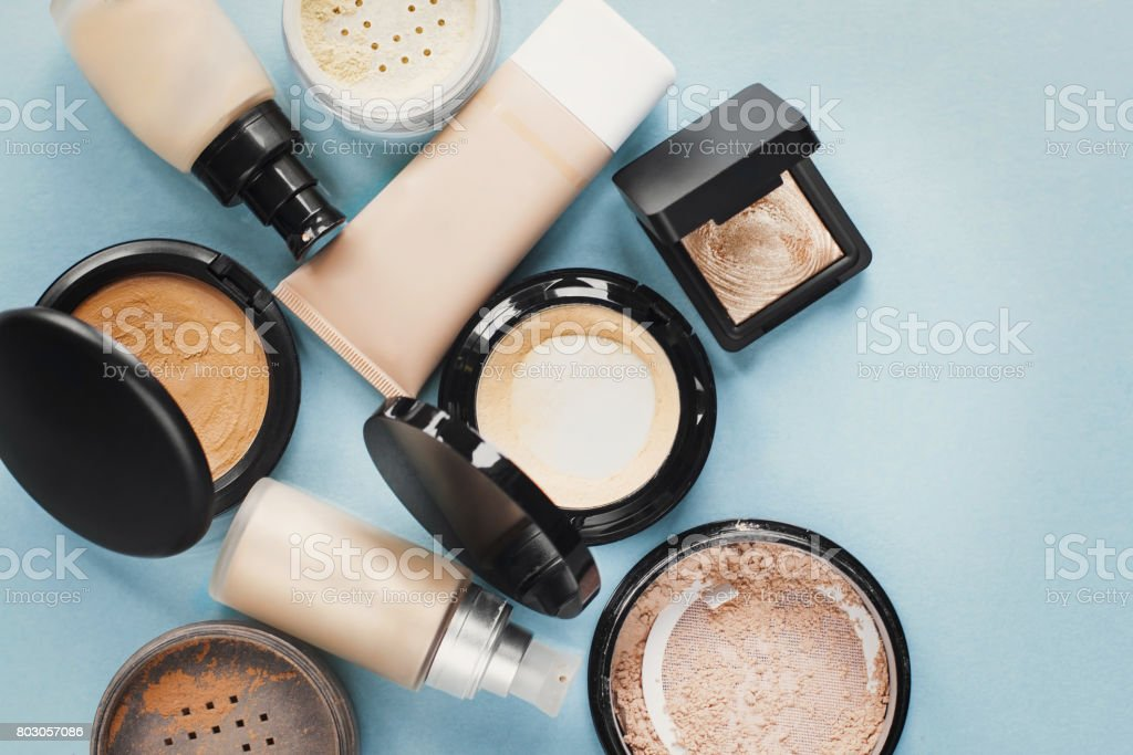 Set of decorative cosmetic. Foundations, facial powders. pastel colored. Blue background. stock photo