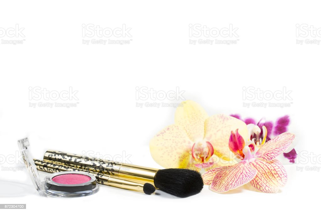 Set of decorative cosmetics of face powder and make-up brush with beautiful orchid flowers stock photo