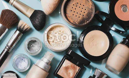 Set of decorative cosmetics. Powder, concealer, eye shadow brush, blush, foundation. Blue background.