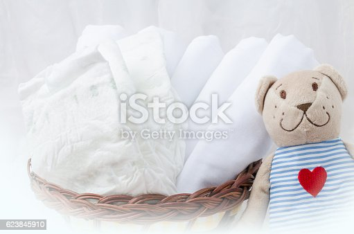 istock Set of diapers for newborn in basket with bear toy. 623845910