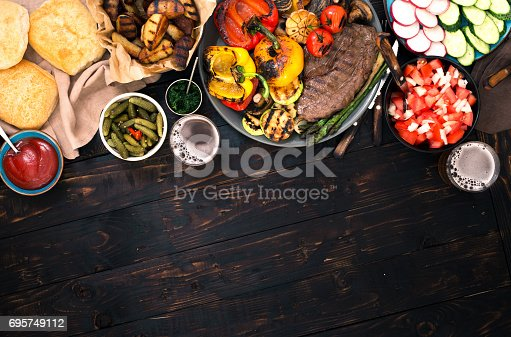 685404620istockphoto Set of different food cooked on grill on dark wooden table with border 695749112