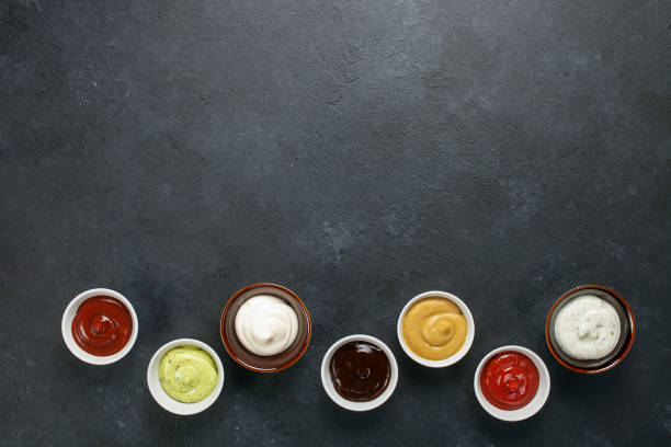 Set of different sauces Set of different sauces - ketchup, mayonnaise, barbecue,  teriyaki, mustard, pesto, adzhika on dark background. Top view. Flat lay. Copy space savory sauce stock pictures, royalty-free photos & images