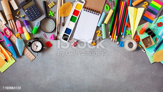 istock Set of different school stationery, alarm clock and supplies on gray background. Back to school concept. Banner format. Top view. 1163684123