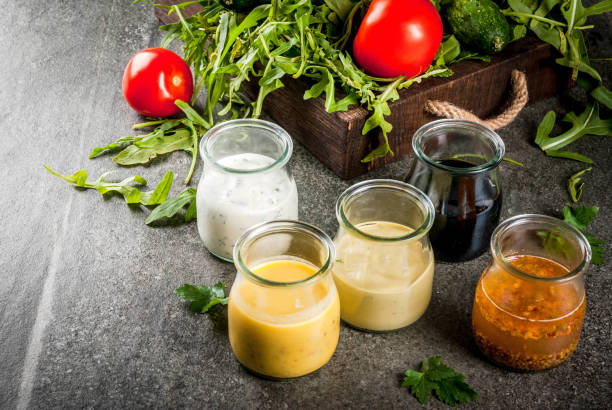 Set of dressings for salad Set of dressings for salad: sauce vinaigrette, mustard, mayonnaise or ranch, balsamic or soy, basil with yogurt. Dark stone table. On background of greenery, vegetables for salad. Copy space salad dressing stock pictures, royalty-free photos & images