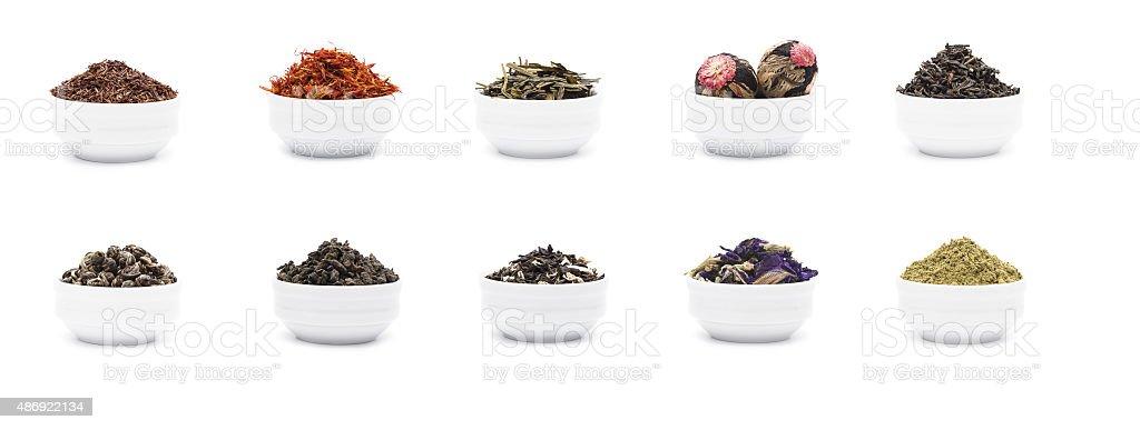 Set of dry tea leaves in white porcelain bowls stock photo