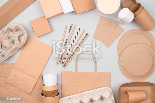 Set of eco-friendly tableware - kraft paper food packaging on light grey background. Street food and fast food paper packaging - cups, plates, straws, containers and paper bags. Copyspace, flat lay