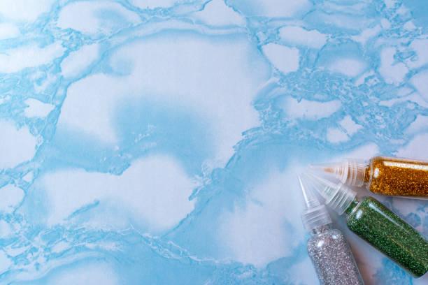 set von smaragd, silber und gold glitzer in plastikflaschen für seifenherstellung auf der oberfläche von blauem marmor, nahaufnahme, volle größe, flach liegen, kopierraum - nägel glitzer stock-fotos und bilder