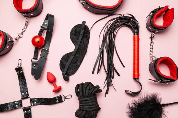 Set of erotic toys for BDSM. The game of sexual slavery with a whip, gag and leather blindfold. Intimate sex games. Set of erotic toys for BDSM. The game of sexual slavery with a whip, gag and leather blindfold. Intimate sex games sex toy stock pictures, royalty-free photos & images