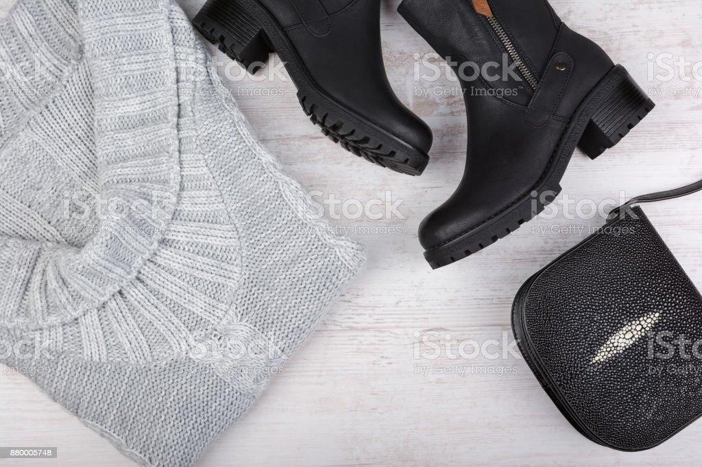 Un ensemble de vêtements pour femmes à la mode d'hiver. Chandail de laine, souliers et sac à main sur un fond en bois blanc. - Photo