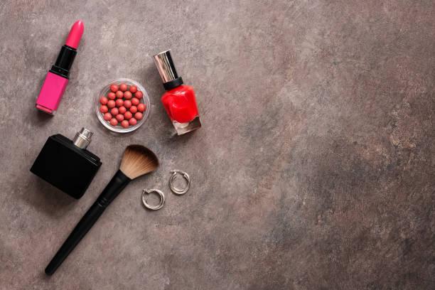 set von weiblichen kosmetika für make-up, nagellack, lippenstift, parfüm, schmuck, erröten mit kugeln und pinsel, dunklen hintergrund. ansicht von oben, flach liegen, kopierraum. - herbst nagellack stock-fotos und bilder