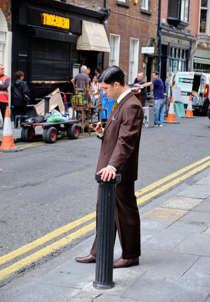 Set of filming on street Dublin, Ireland, July 6, 2017: Actor in a time piece during a filming break looking at cell phone in front of Trocadero. Crew visible in background anachronistic stock pictures, royalty-free photos & images