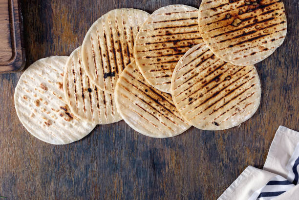 set of flatbread cooked on a grill on a wooden table - tortilla stock photos and pictures