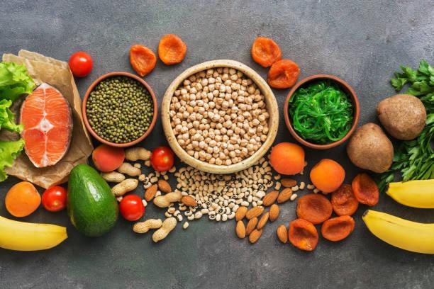 een set van voedingsmiddelen hoog in kalium op een rij op een donkere achtergrond. gezonde evenwichtige maaltijd. bovenaanzicht, plat lag. - kalium stockfoto's en -beelden