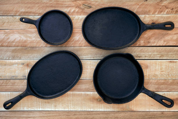 Set of four round and oval cast iron skillets of different sizes on a wooden background. stock photo
