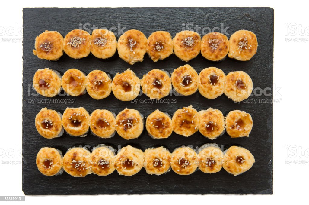 Set of fried sushi rolls with fish and rice on black stone slate stock photo